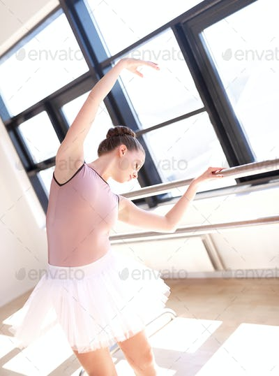 Ballerina Stretching at Barre in Dance Studio