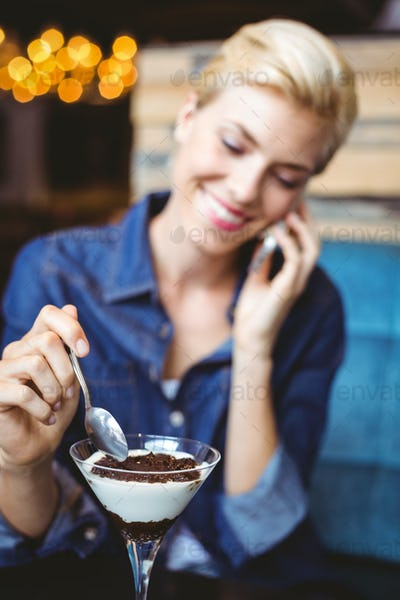 Smiling blonde eating a creamy chocolate while on the phone
