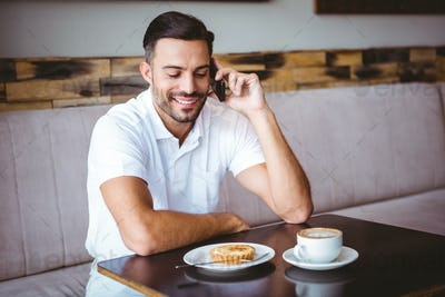 Young man smiling on the phone at the cafe
