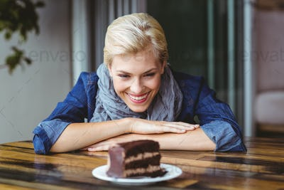 Smiling blonde looking a chocolate cake at the cafe