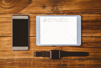 Tablet next to smartphone and swatch on wooden table