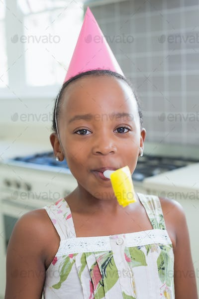 Happy girl celebrating a birthday at home in the kitchen