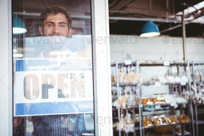 Smiling worker putting up open sign at the bakery