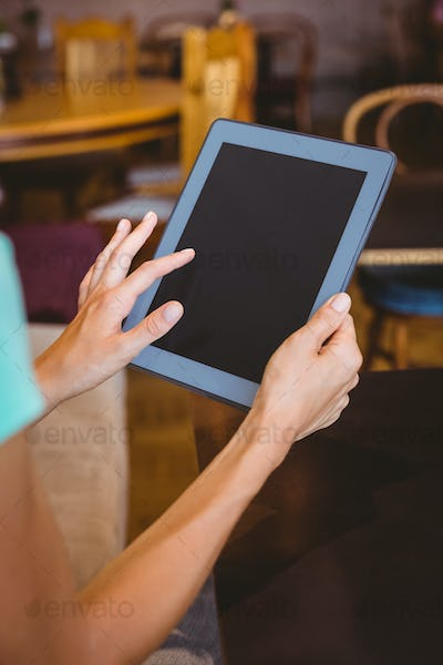 A woman using tablet computer at the cafe