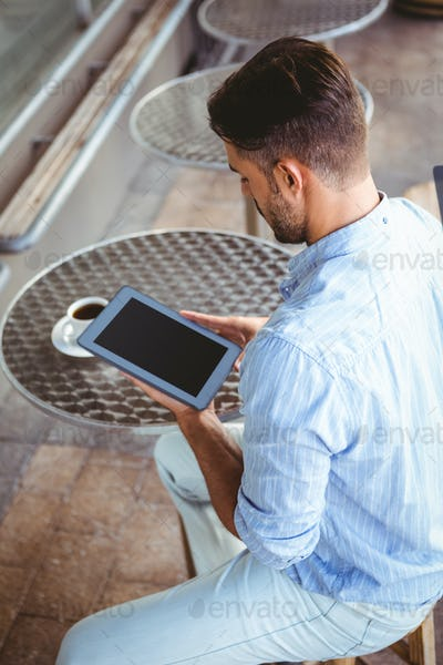 Shoulder view of attentive businessman using a tablet outside the cafe