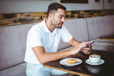 Young man having cup of coffee and pastry while texting in a cafe