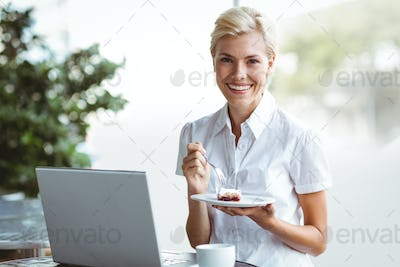 Young woman having a piece of pie using laptop in a caffe