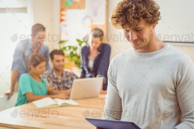 Young casual businessman using digital tablet with colleagues behind in the office