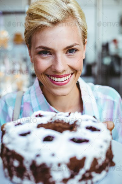 Portrait of a pretty woman looking at a chocolate cake