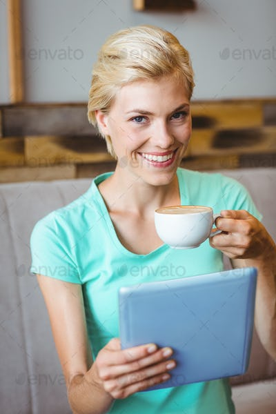 Pretty blonde holding cup of coffee and using tablet computer at the cafe