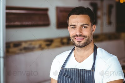 Handsome waiter smiling at camera at the cafe