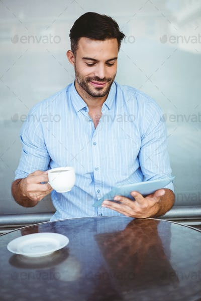 Smiling businessman using a tablet while drinking coffee outside the cafe