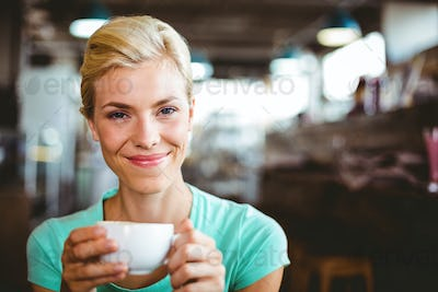 Pretty blonde holding cup of coffee at the cafe