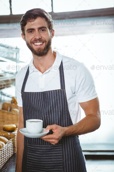 happy worker in apron holding a cup of coffee at the bakery