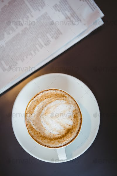 Close up view of a cappuccino beside a newspaper