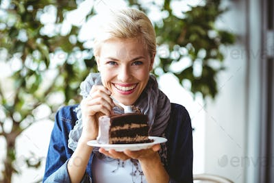 Portrait of a smiling blonde taking a piece of chocolate cake