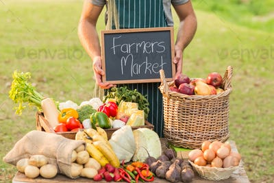 Farmer standing at his stall and holding chalkboard on a sunny day