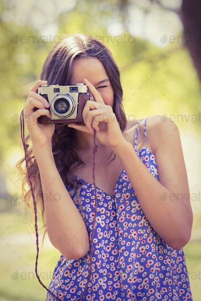 Pretty brunette in the park using retro camera on a sunny day
