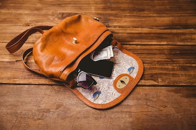 Sunglasses and wallet on the vintage bag on wooden table