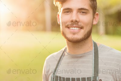 Handsome farmer smiling at camera on a sunny day
