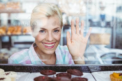 Pretty woman gesturing a greeting at the bakery
