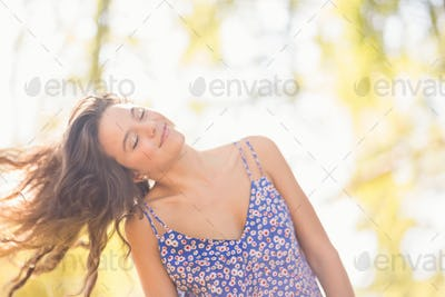Pretty brunette tossing her hairs on a sunny day