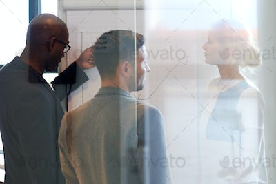Three colleagues standing looking at a chart
