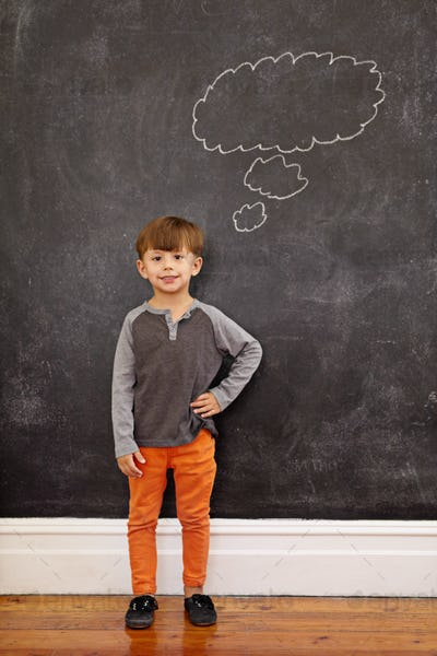 Cute little boy with a thought bubble on the blackboard