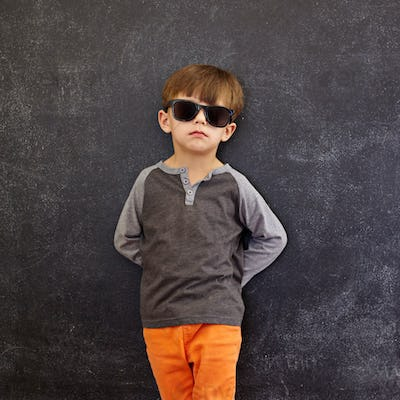 Stylish little boy wearing sunglasses leaning on a blackboard