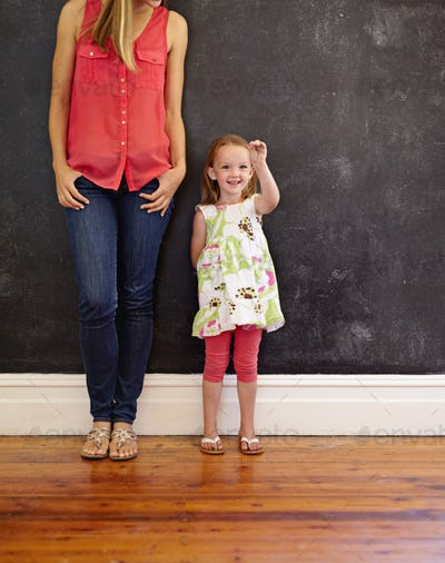 Mother and daughter standing together - Indoors