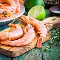 fresh raw prawns on a wooden cutting board with salt, pepper, lime