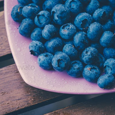 Old bowl of fresh organic blueberries on wooden table.Soft focus