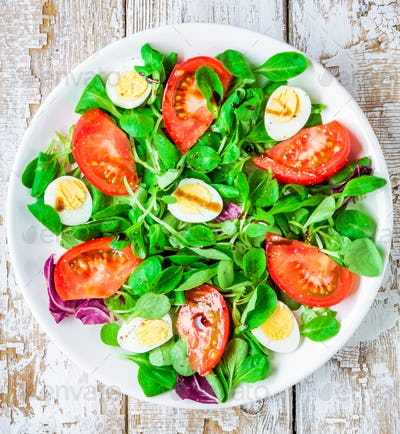 fresh green salad with lamb's lettuce, tomatoes and quail eggs