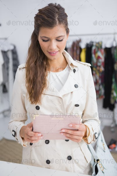 Smiling woman opening her wallet at a boutique