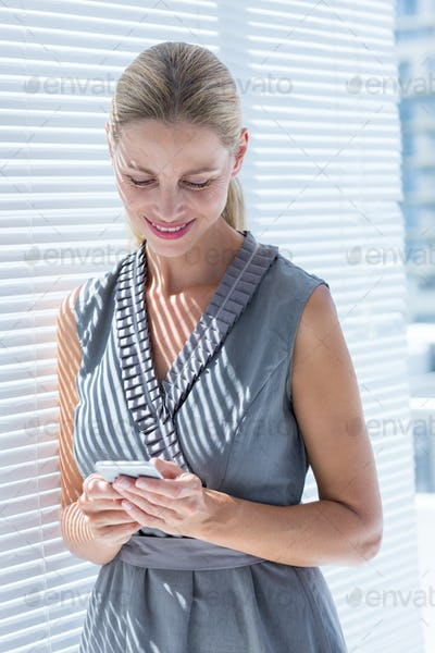 Smiling businesswoman looking her smartphone in the office