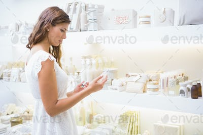 Concentrated woman reading ingredients at a beauty salon