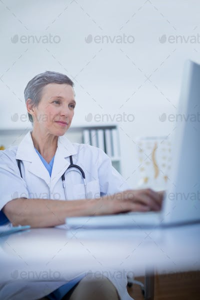 Female doctor using her laptop computer in medical office