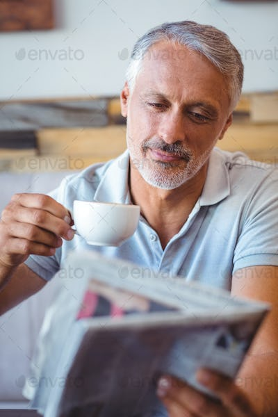 Smiling man having cup of coffee reading newspaper at the cafe
