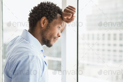 Young concentrated businessman looking out of the window and leaning against it in the office