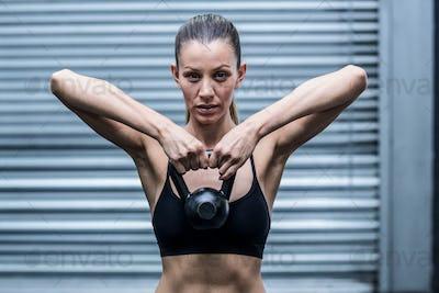 Portrait of a muscular woman lifting kettlebells