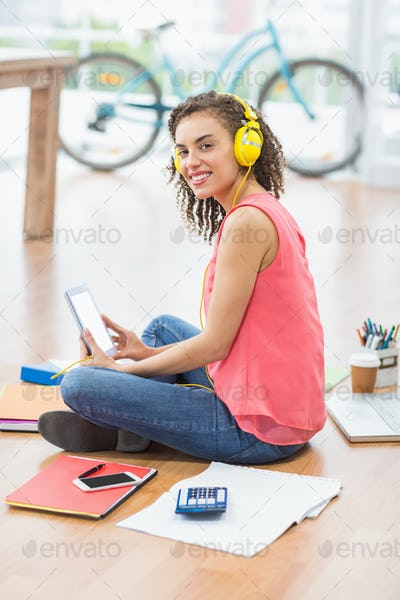 Young creative businesswoman holding a tablet while looking at the camera