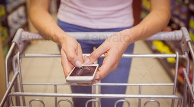 Close up view of woman using smartphone in supermarket