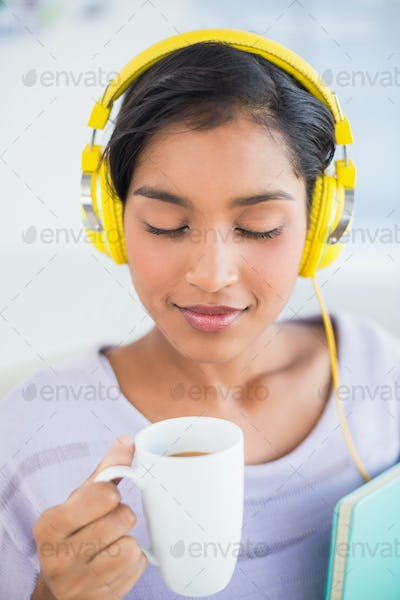 Smiling woman listening to headphones holding a cup of coffee