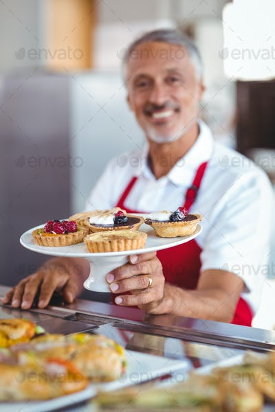 Barista holding a plate of pastries in the bakery
