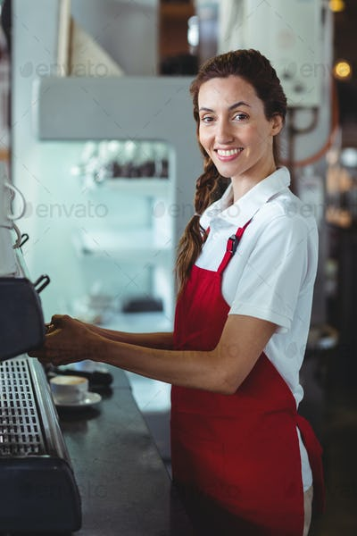 Pretty barista looking at camera and using the coffee machine at the cafe
