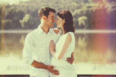 Happy and young pregnant couple hugging in nature at the lake. V