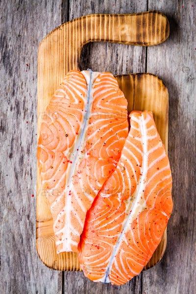 fresh raw salmon fillet on a wooden cutting board