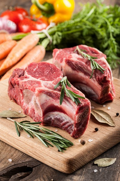 Raw beef meat on cutting board and fresh vegetables