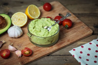 Guacamole on wooden table surrounded by its ingredients