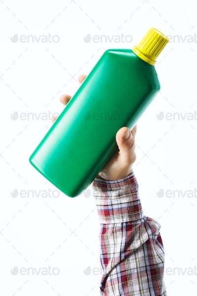 Hand holding a fertilizer bottle